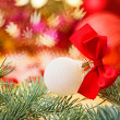 Christmas ball with red bow on blurred decoration background — Stock Photo