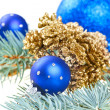 Blue Christmas decoration balls with golden cones on fir branch — Stock Photo