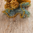 Christmas golden decorations on pine branch on wooden background — Stock fotografie
