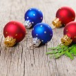 Stock Photo: Christmas balls on wooden background with green thuja branch