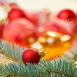 Red decoration ball with spruce branch on blurred Christmas back - Stock fotografie