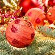 Royalty-Free Stock Photo: Red decoration ball with spruce branch on blurred  Christmas bac