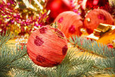 Red decoration ball with spruce branch on blurred Christmas bac — Stock Photo