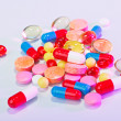Pills, tablets and drugs heap, medical concept in violet colors - Stock Photo