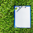 Blue medical clipboard with a pen over lush green clover grass — Stock Photo