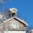 Old wooden snow covered chapel with clock — Stock Photo