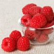 Still life with red raspberry and glass bowl on gray linen table — Stock Photo