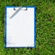 Blue medical clipboard with a pen over lush green grass — Stock Photo