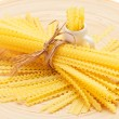 Pasta bunch composition on a wooden plate, closeup view - Stock Photo