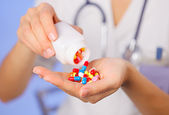 Pills, tablets and drugs pouring from bottle in doctor's hand on — Stockfoto