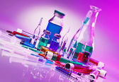 Medical laboratory glass equipment still life on blue purple — Stock Photo