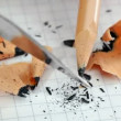 Sharpening the pencil with a penknife on squared paper background — Stock Video