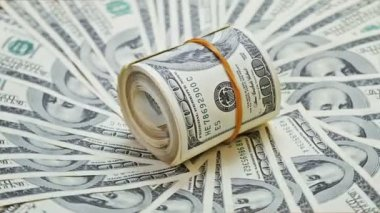 Rotating rolled up bundle of 100 dollar notes on a money background — Stock Video
