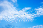 Blue sky with fleecy clouds background — Stock Photo