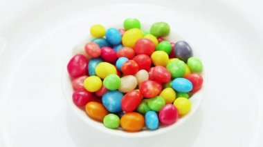 Multicolor bonbon sweets (ball candies) rotating on white plate, loop ready — Stock Video