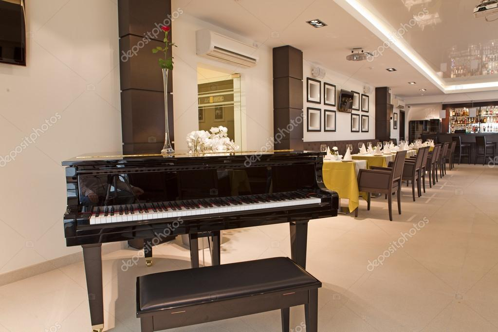Real interior of restaurant with a piano — Stock Photo #12377544