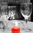 Burning candle on the served table against a fireplace - Stock Photo