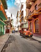 HAVANA, CUBA-MAY 14: Street scene with an old rusty american car — Stock Photo