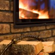 Fire wood against a fireplace — Stock Photo #8943940