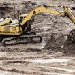 Digging excavator machine at building construction site - Stock Photo