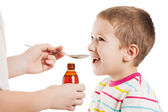 Doctor giving spoon of syrup to child boy — Stock Photo