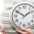 Pregnant woman hand holding large office wall clock showing time — Stockfoto