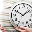 Pregnant woman hand holding large office wall clock showing time - Stock Photo