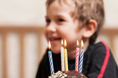 Smiling child with birthday cake candle — Stock Photo