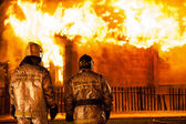 Firefighters at burning fire flame on wooden house roof — Stock Photo