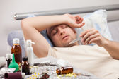 Unwell man patient lying down bed — Stock Photo