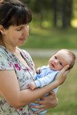 Cute little newborn baby child on mother hands walking outdoor — Stock Photo