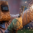 Arc welder worker in protective mask welding metal construction — Stock Photo #28947347