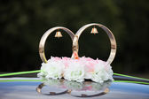 Gold rings and rose flowers on wedding car — Stock Photo