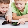 Two smiling child boys playing games or surfing internet on tabl — Stock Photo #39121387