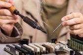 Human hand holding soldering iron repairing computer circuit boa — Stock Photo
