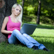Beautiful young blond woman sitting outdoor — Stock Photo #28862547