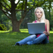 Beautiful young blond woman sitting outdoor — Stock Photo