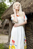 Landsbygdens kvinna som står vid gamla huset — Stockfoto