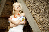 Rural woman sitting near by old traditional Ukrainian barn — Stock Photo