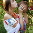 Beautiful ukrainian girl in traditional dress drinking milk — Stock Photo