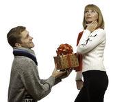 Ung man ger en gåva till vacker ung kvinna — Stockfoto