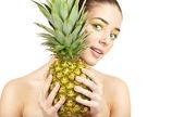 Beauty. Young beautiful woman holding pineapple — Stock Photo