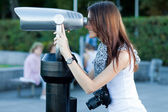 Young woman tourist looks through a telescope — Стоковое фото