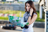 Young woman tourist holding paper map — Stock Photo