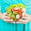 Woman holding plate of vegetable salad — Stock Photo