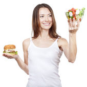 Beautiful young woman holding hamburger and salad — Stock Photo