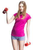 Young beautiful blond girl holding dumbbells — Stock Photo
