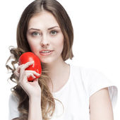 Young beautiful brunette woman holding red pepper — Stock Photo