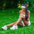 Injured sportswoman sitting on the grass — Stockfoto