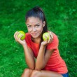 Young beautiful brunette woman holding two apples — Stock Photo #31086227